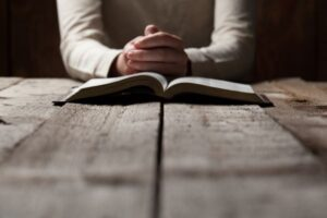 woman praying to Jesus over Bible a promise honored